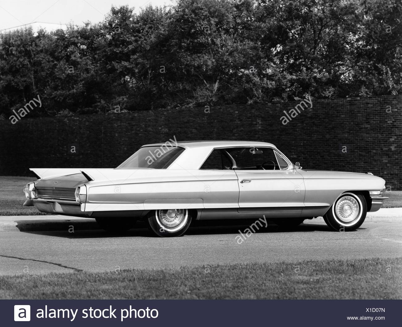 Side profile of a coupe parked on a road, 1962 Cadillac Series 62 - Stock Image