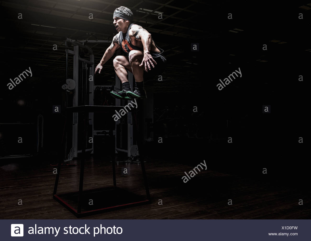 Young man leaping in gym Stock Photo