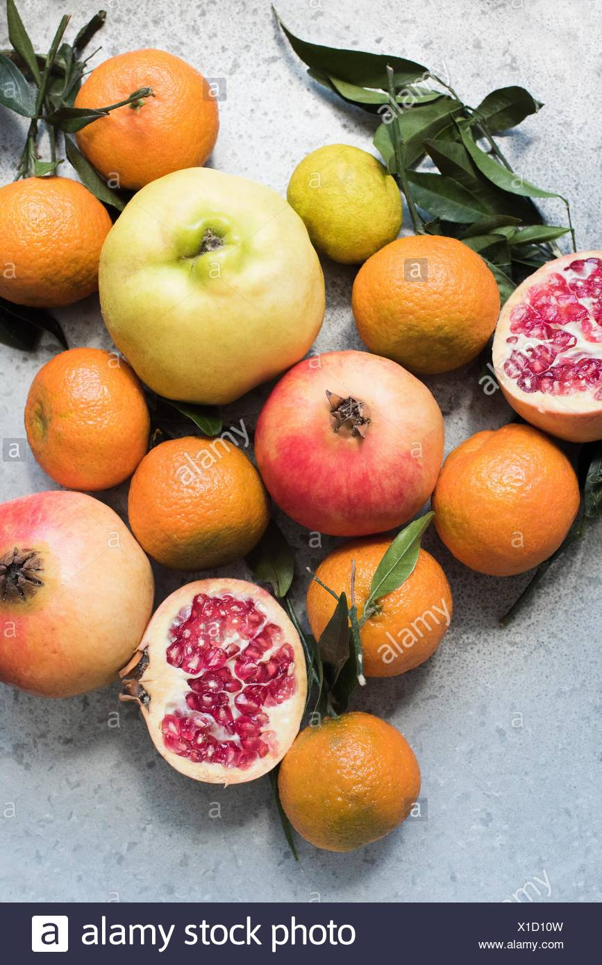 Overhead view of colourful fruits and halved pomegranate - Stock Image