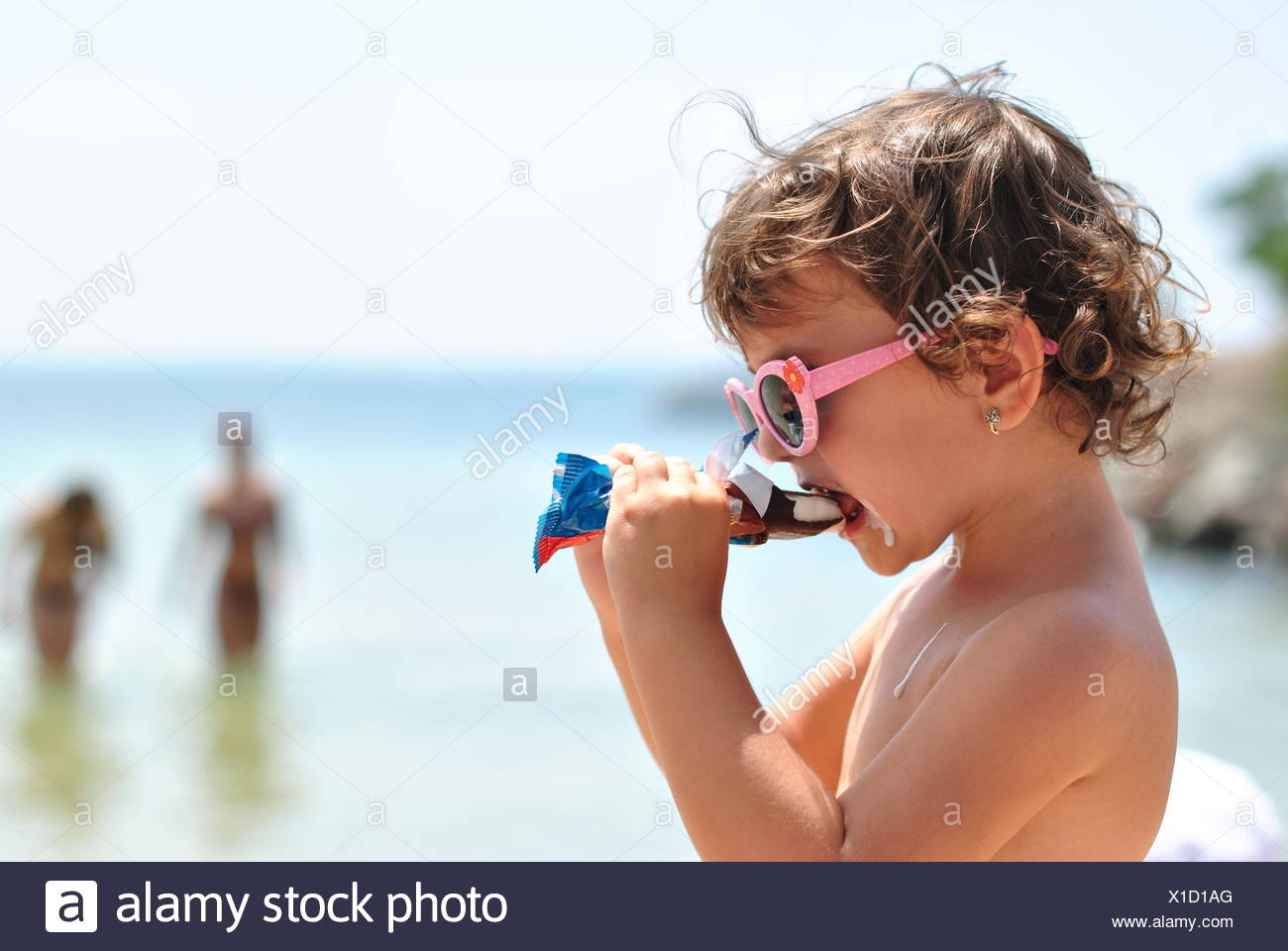 little girl eating ice cream on the beach of sea Stock Photo