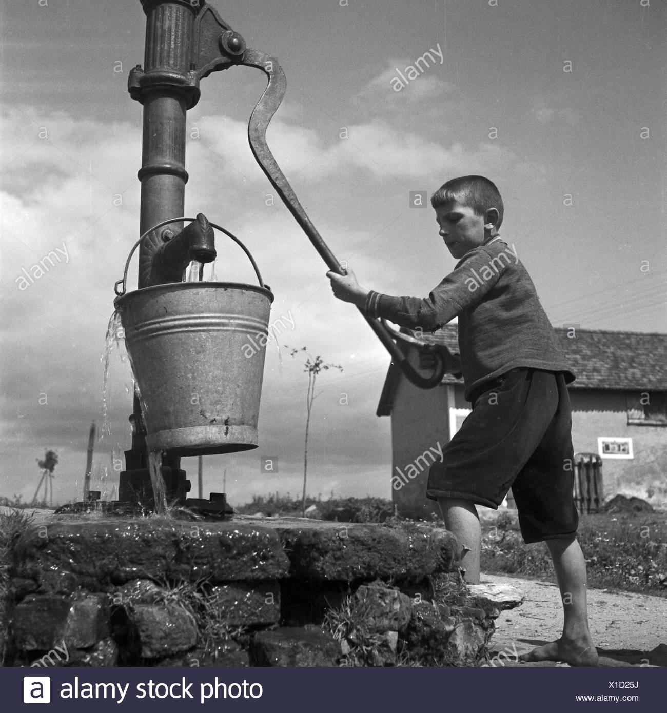 Ein Junge holt Wasser an einem Brunnen in Allenstein in Ostpreußen, Deutschland 1930er Jahre. A boy taking water from a well at Allenstein in East Prussia, Germany 1930s. - Stock Image