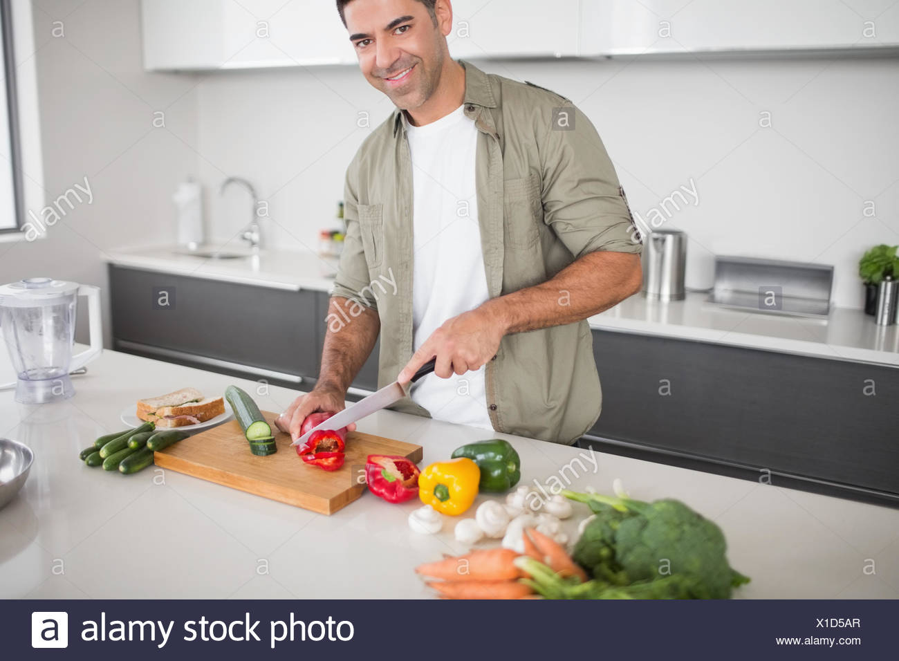 Smiling man chopping vegetables in kitchen - Stock Image