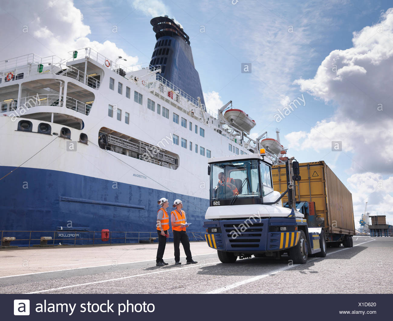 Port workers on dock side beside ship - Stock Image