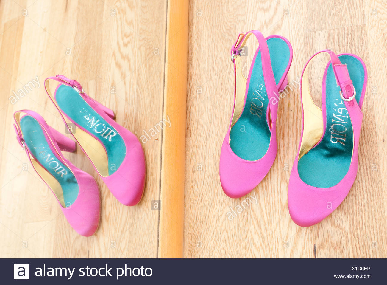 Bridal shoes standing in front of a mirror on parquet flooring - Stock Image