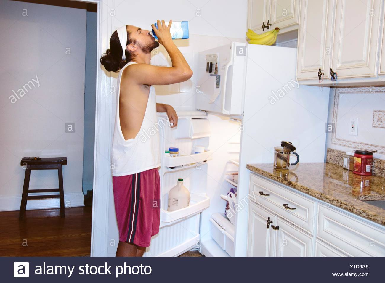Young man standing next to open fridge, drinking milk from carton - Stock Image