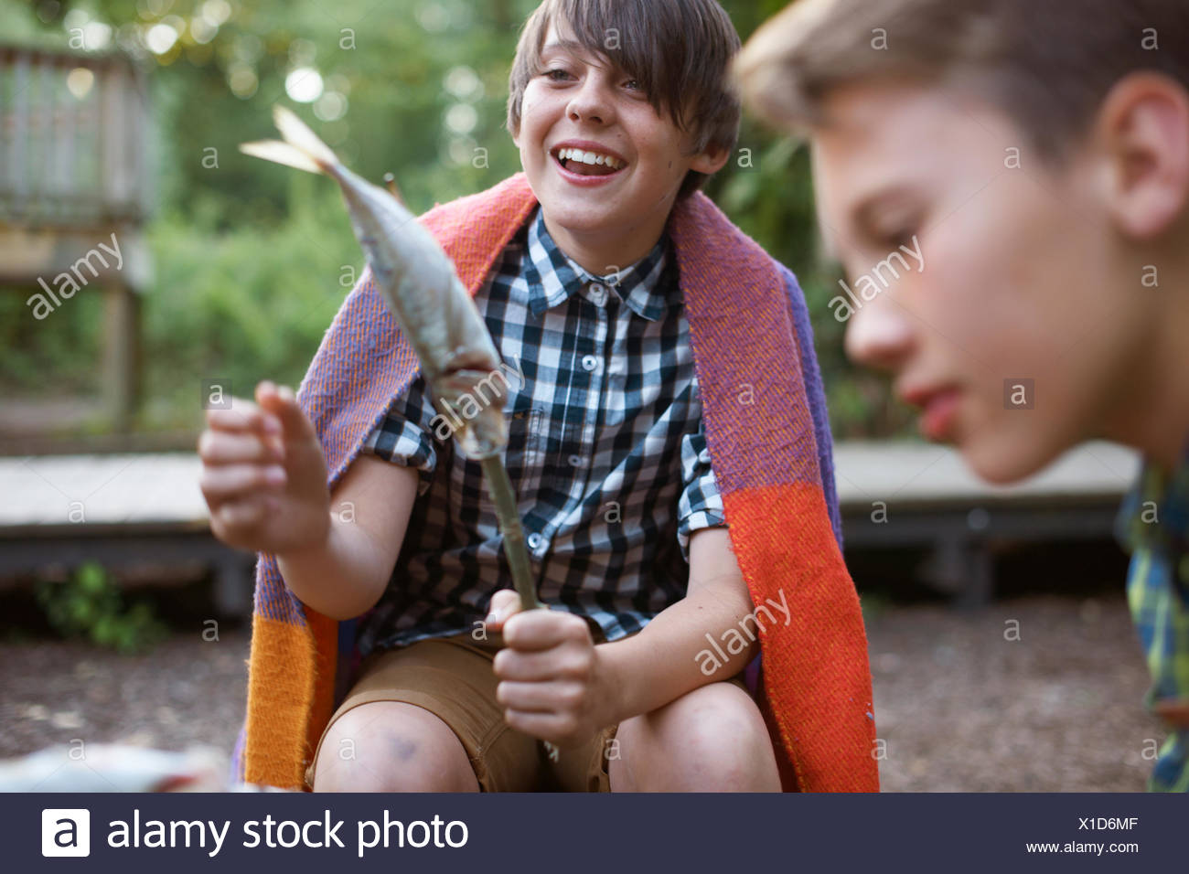 Young boy holding stick with fish on ready to barbecue Stock Photo