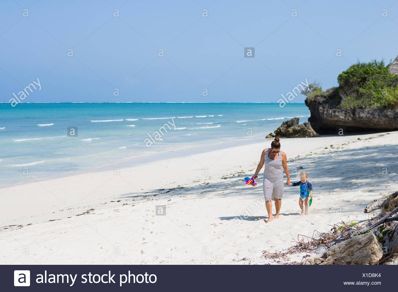 Mother and son walking on Diani Beach, Kenya - Stock Image