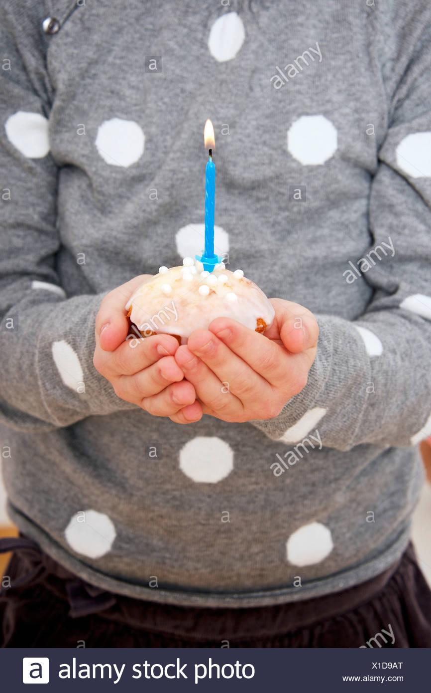 Child on birthday party holding cupcake with burning candle, Munich, Bavaria, Germany - Stock Image