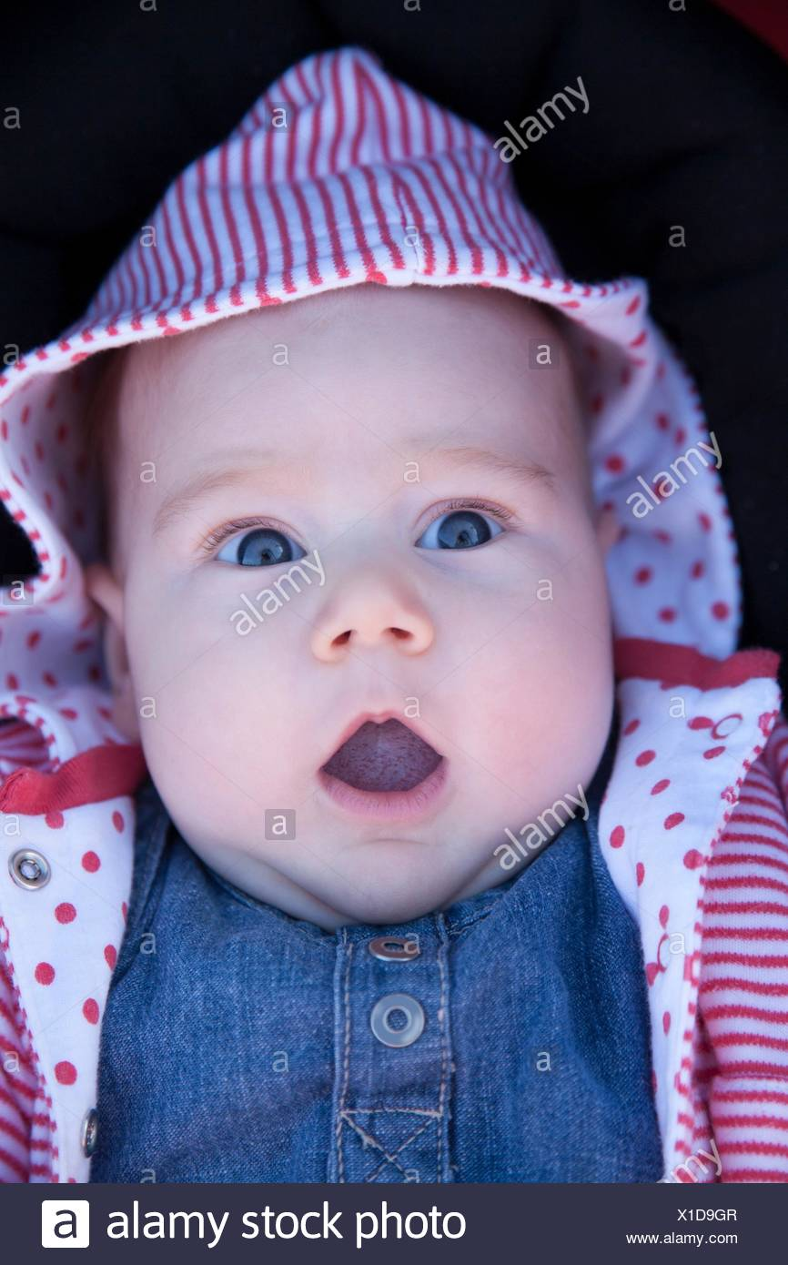 three month baby with jeans dress looking at camera with horror fright face. - Stock Image