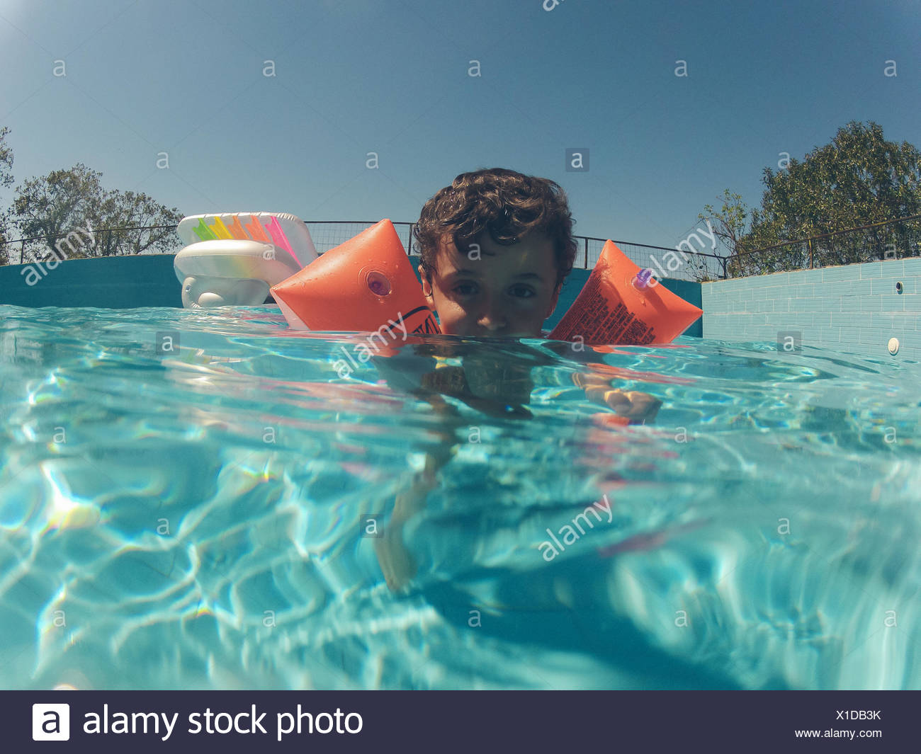 Portrait Of Boy Swimming In Pool With Water Wings - Stock Image