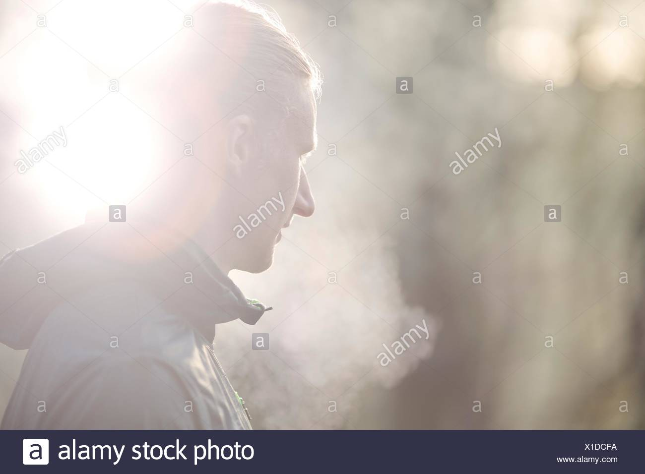 Side view of mid adult man looking away, condensation from breath - Stock Image