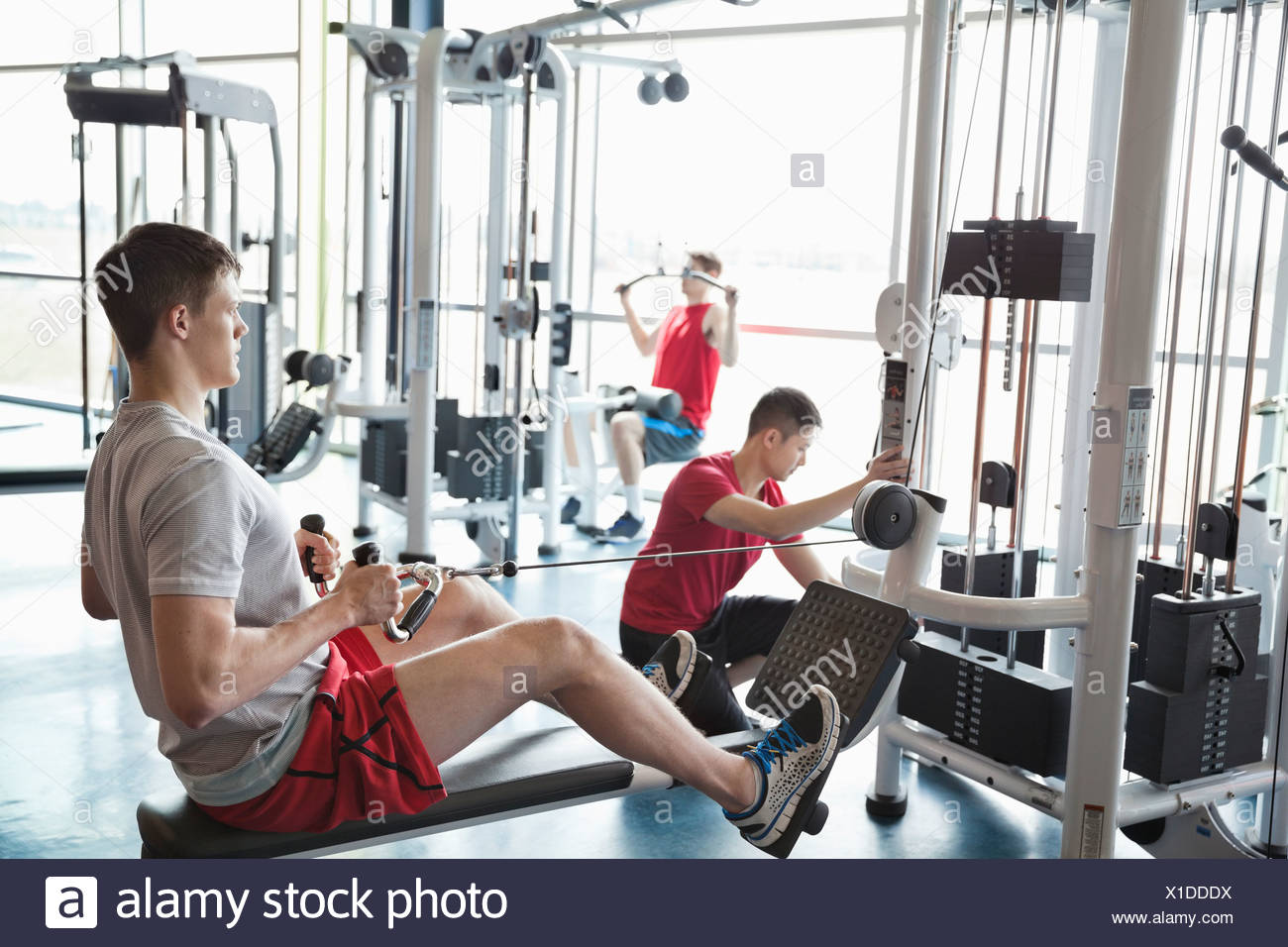 Men using weight machines in fitness center - Stock Image