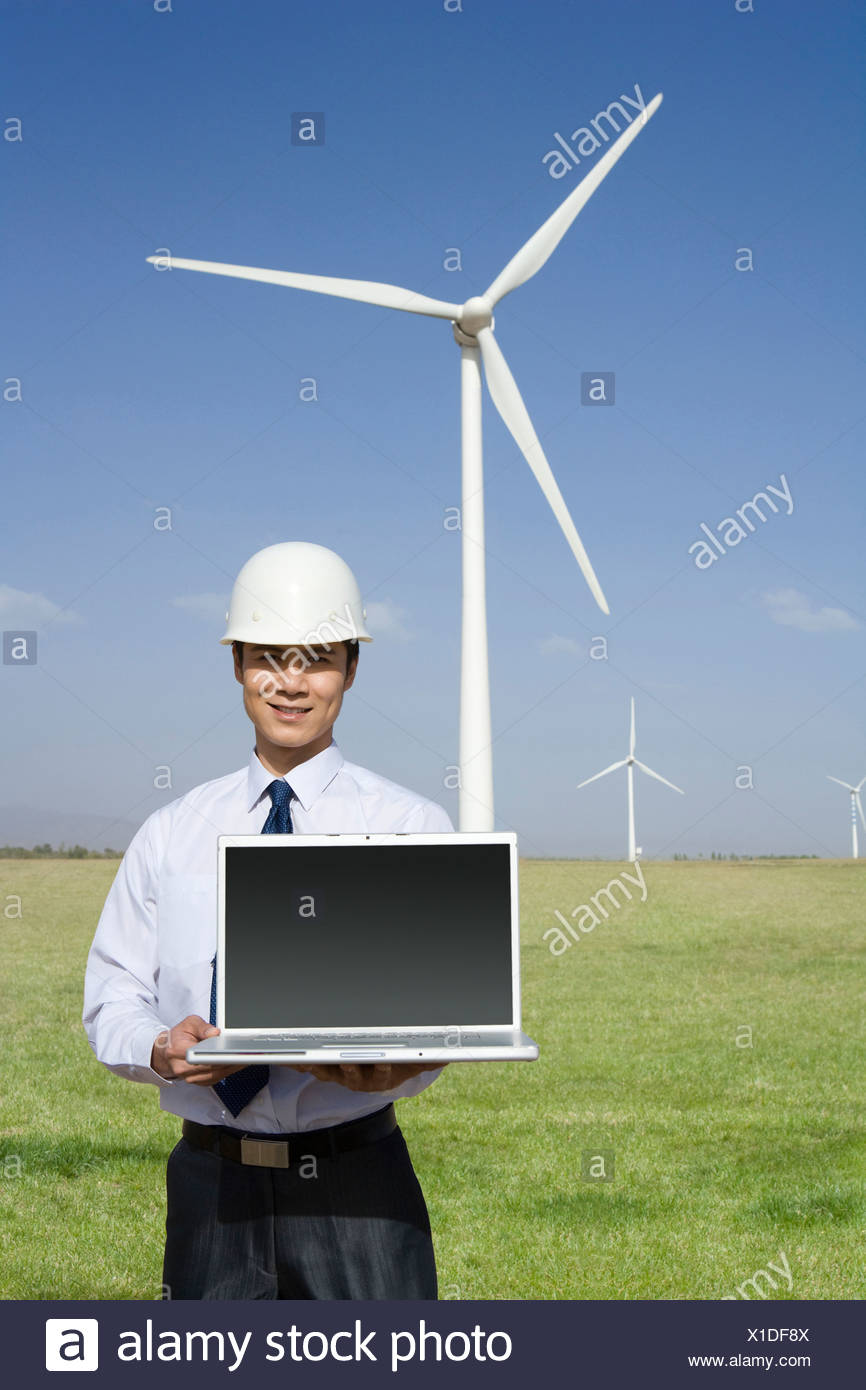Engineer holding a laptop in front of wind turbines - Stock Image