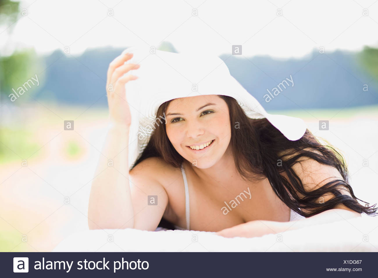 young plump girl lying on a sun lounger - Stock Image
