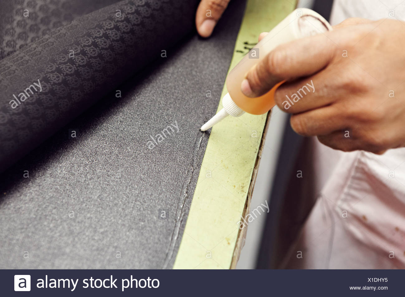 Close up of hands gluing fabric - Stock Image