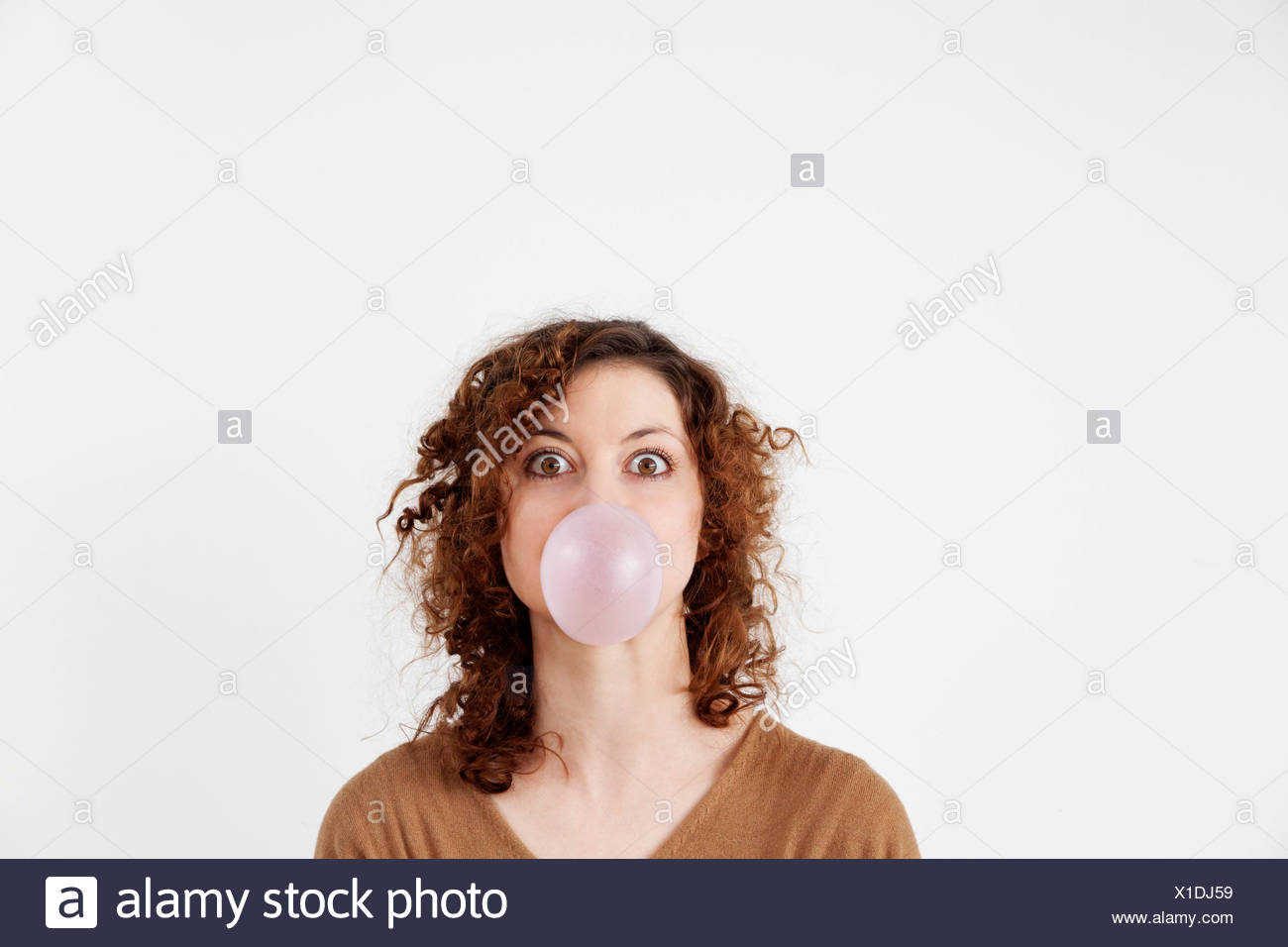 Young woman blowing a chewing gum bubble - Stock Image