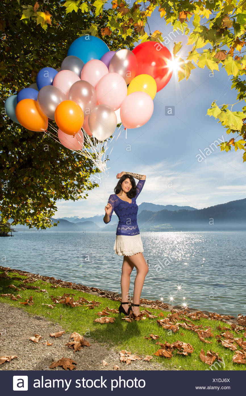 Young woman in blue top and white short skirt posi Stock Photo