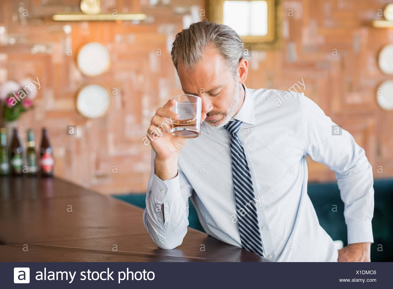 Businessman clutching whiskey glass to forehead - Stock Image