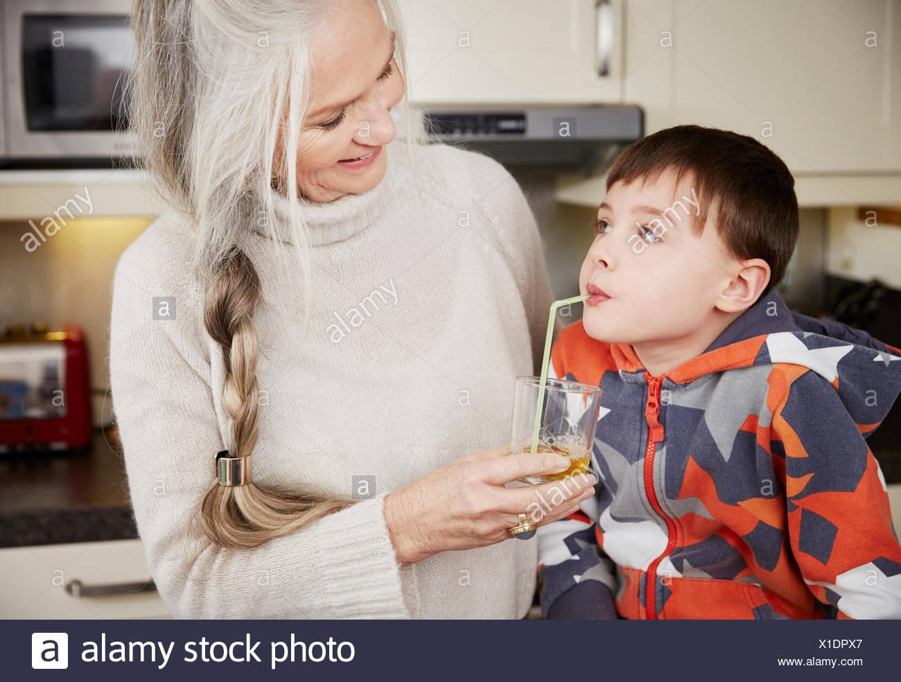 Grandmother offering grandson drink - Stock Image