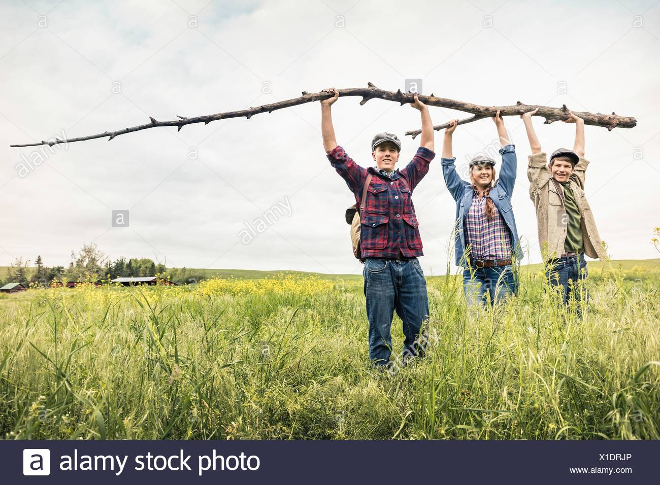 Young adults and teen boy in tall grass holding up branch looking at camera smiling - Stock Image