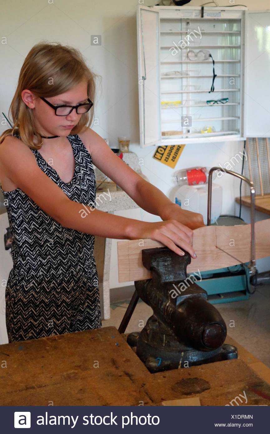 6th Grade Girl Using Coping Saw With Vice in Technology Class, Wellsville, New York, USA. - Stock Image