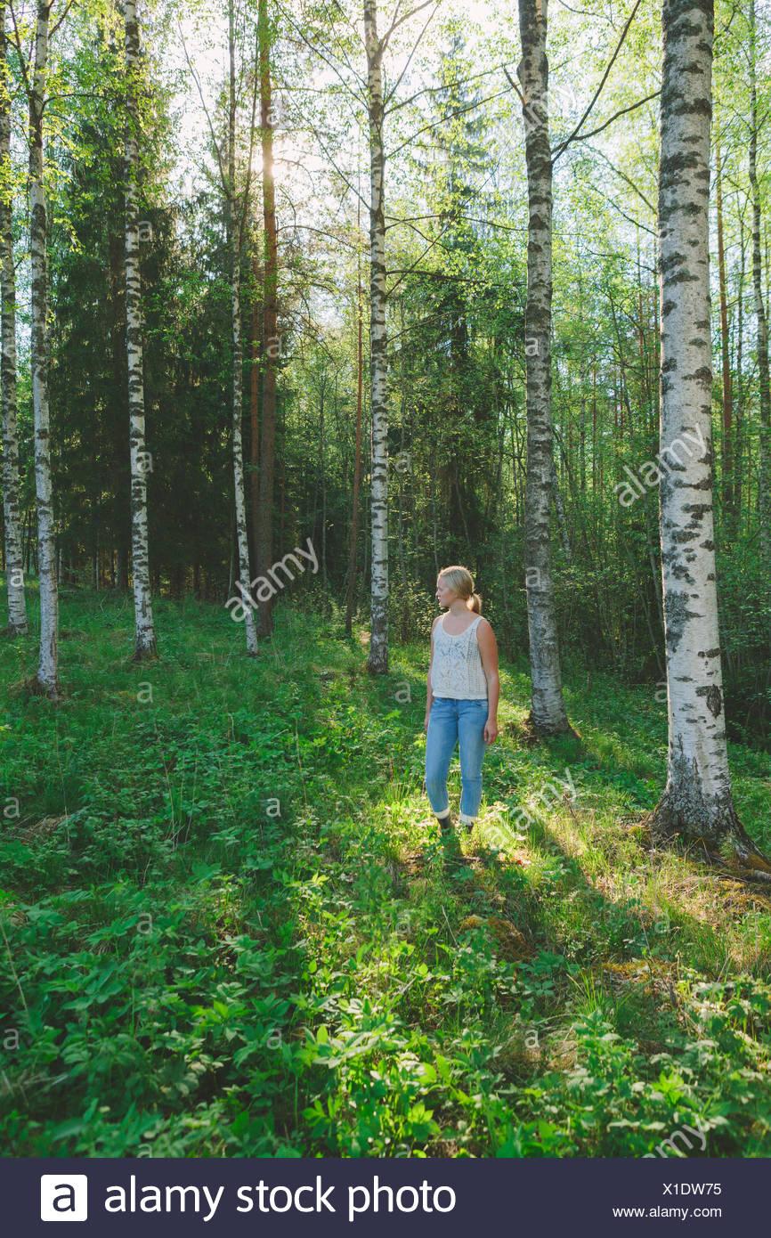 Finland, Mellersta Finland, Jyvaskyla, Saakoski, Woman standing in forest glade - Stock Image
