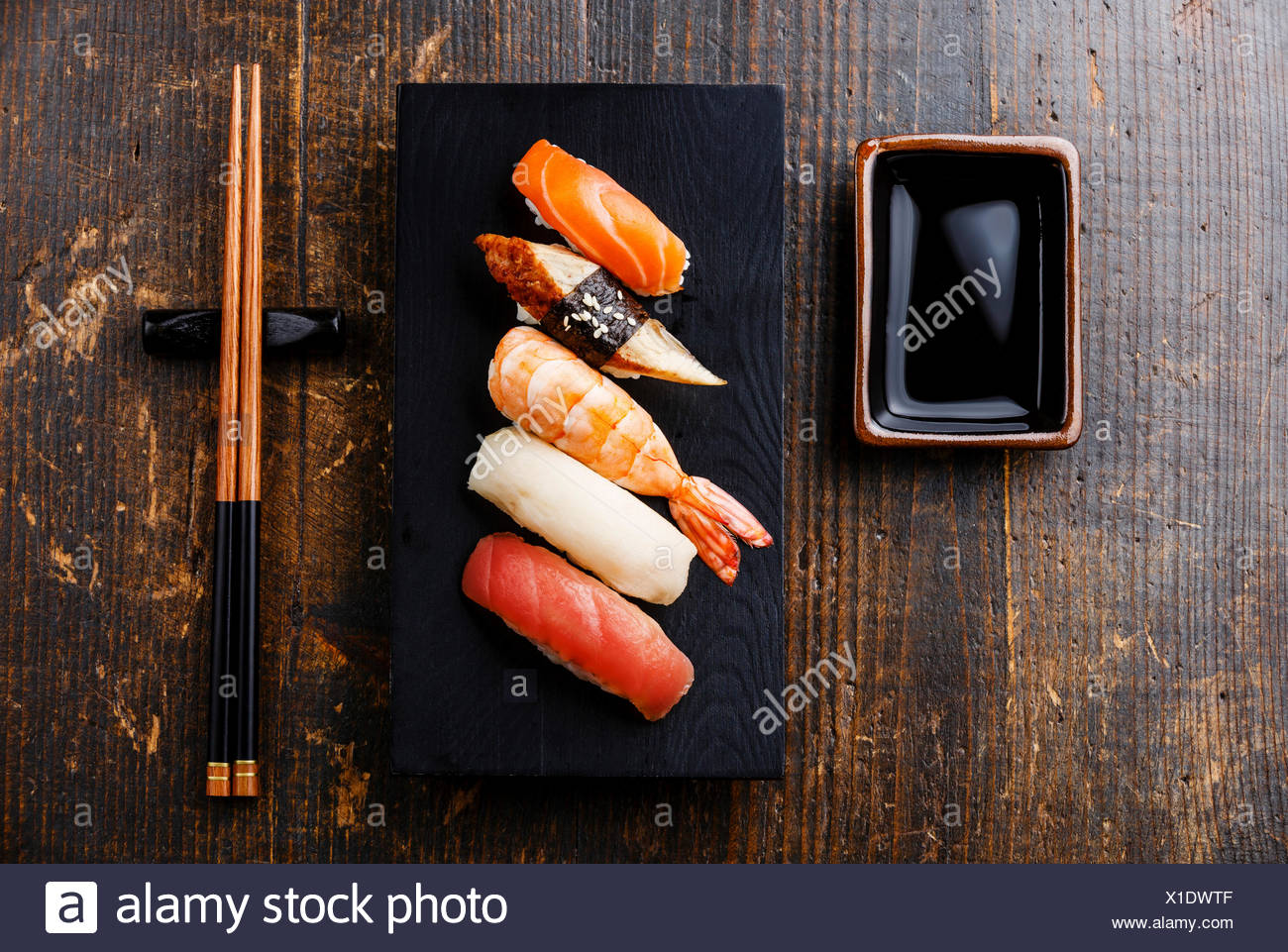 Nigiri sushi set and soy sauce on wooden table background - Stock Image