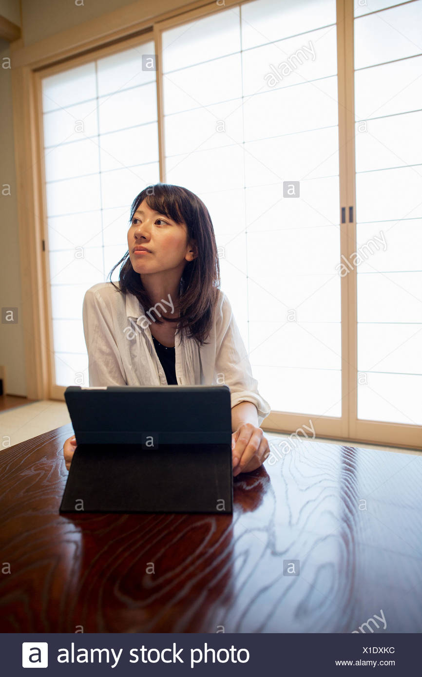 A woman sitting at a table with a laptop computer. - Stock Image