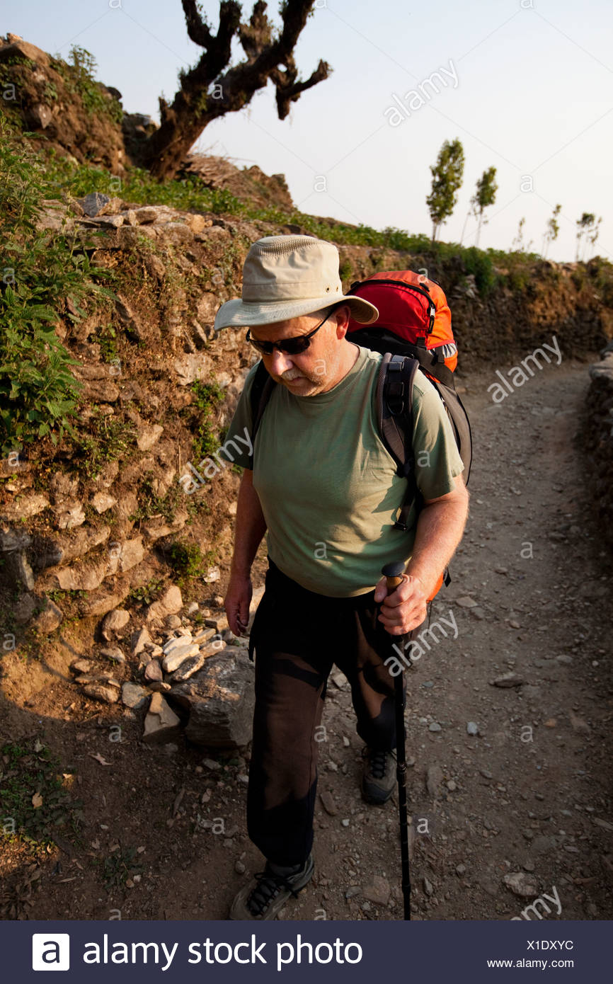 A trekker puts his head down and marches uphill in Nepal. - Stock Image