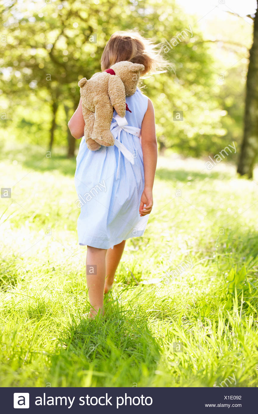 Young Girl Walking Through Summer Field Carrying Teddy Bear Stock Photo