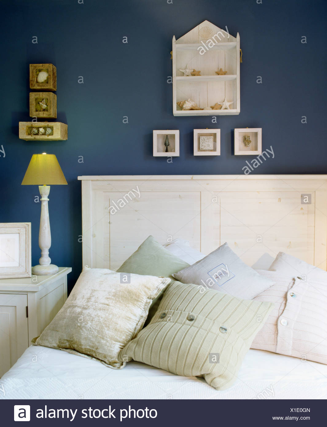 Small wooden shelf unit and pictures above white wooden bed with silk cushions in dark blue