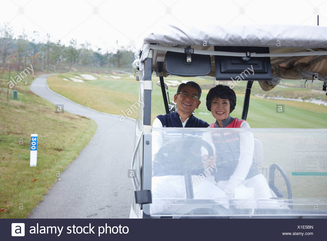middle aged couple on golf cart - Stock Image