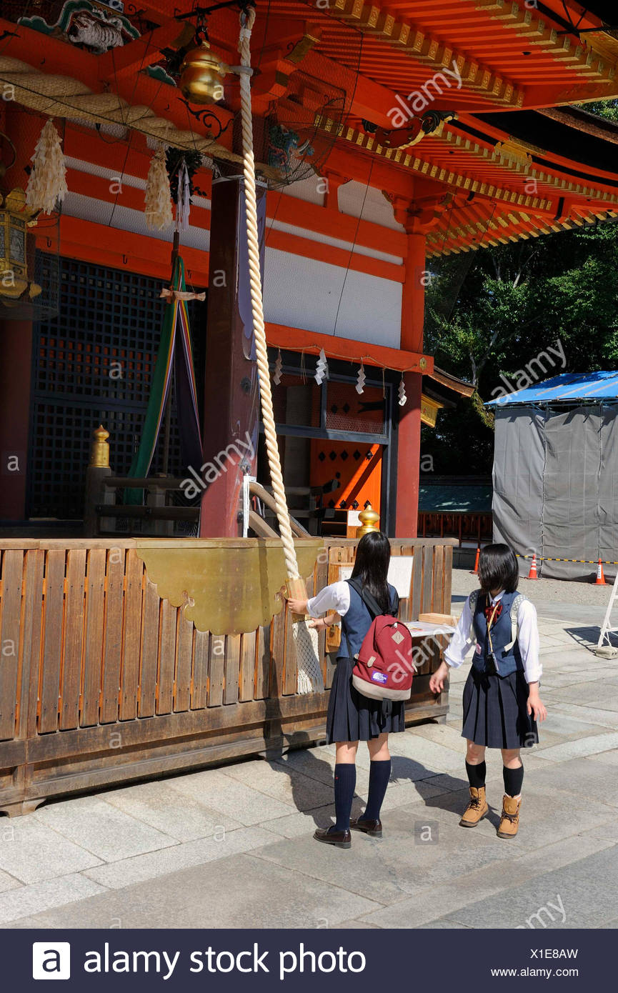 Students wearing school uniforms ringing the bell on a shrine to draw the spirits' attention to them, Yasaka Shrine - Stock Image