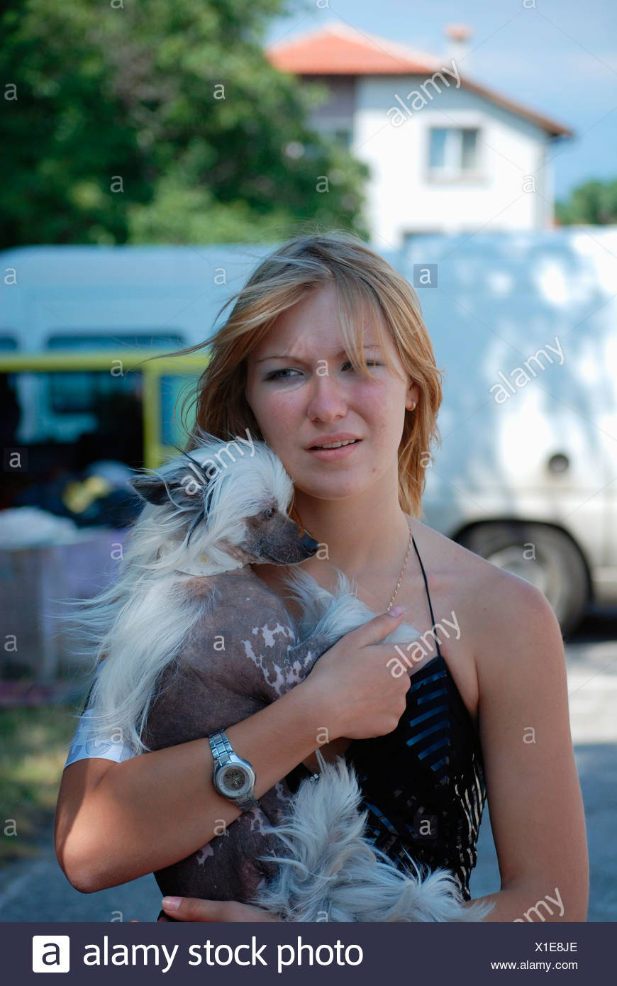 A woman with a chinese crested dog - Stock Image