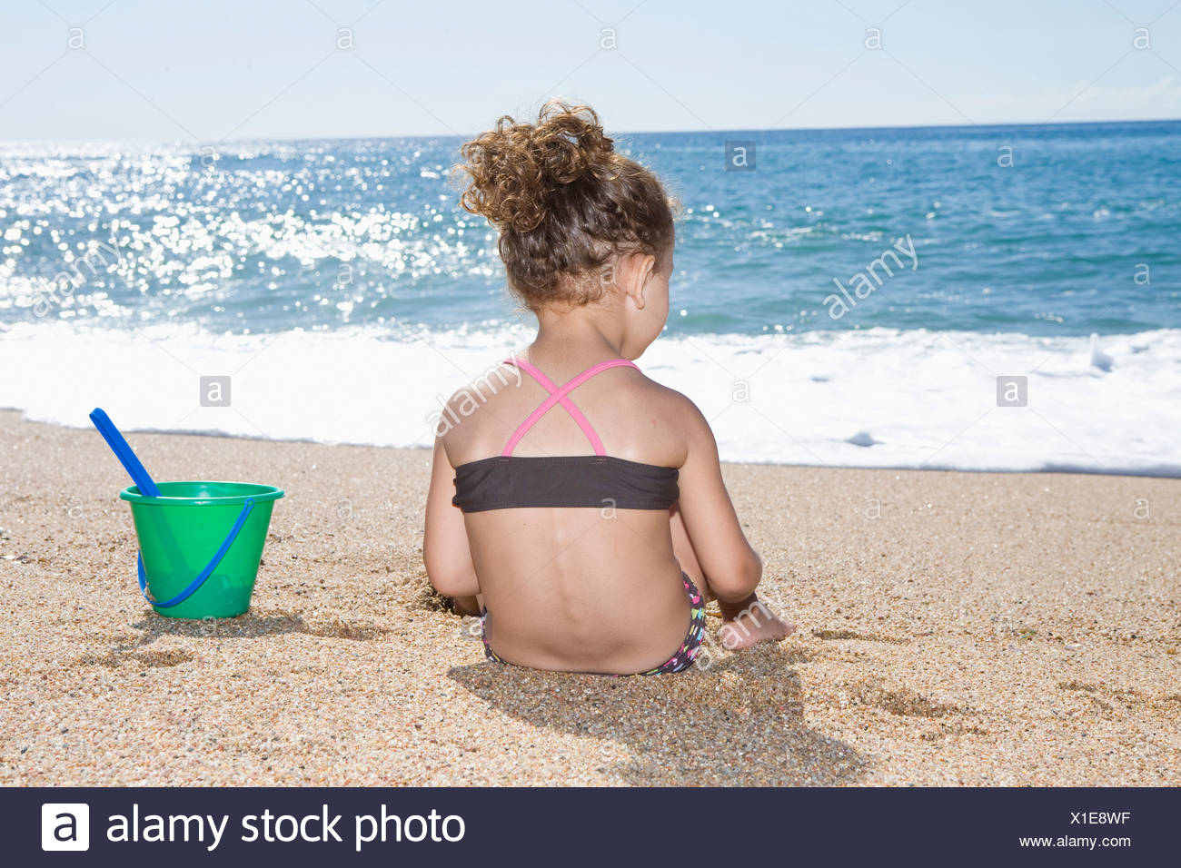 France, Corsica, Girl (2-3) siting on beach, rear view - Stock Image