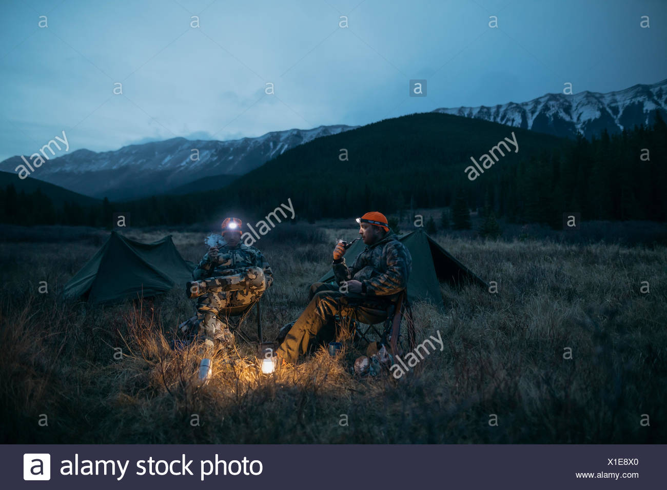 Male hunter friends in camouflage and headlamps at campsite in remote field below mountains at night - Stock Image