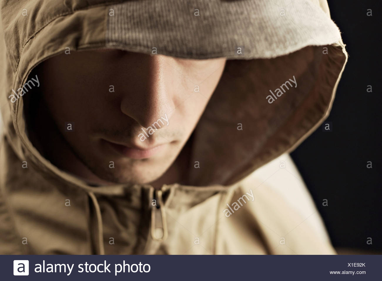Young man wearing hood jacket, close-up - Stock Image