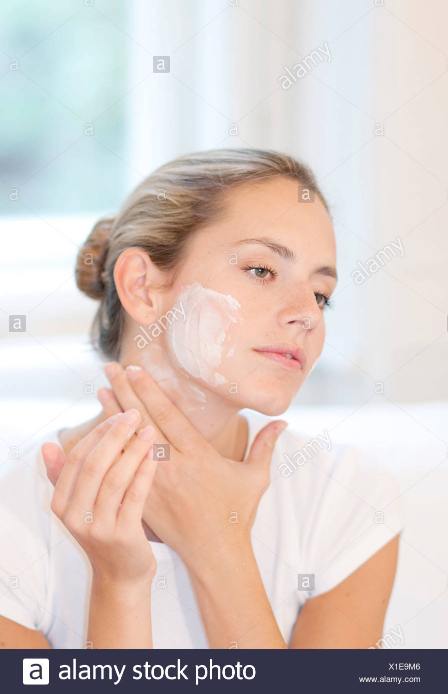 Female highlighted fair hair off her face, wearing a white t shirt, applying face cream to her cheeks and neck, unsmiling, - Stock Image