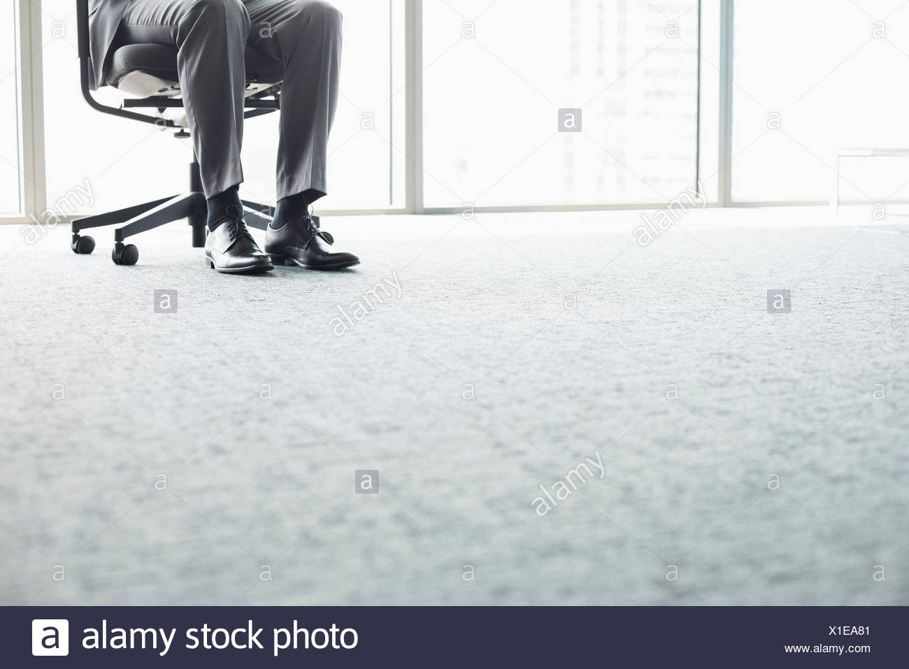 Low section of businessman sitting on office chair - Stock Image