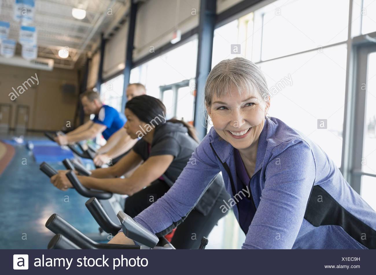 Smiling woman on exercise bike - Stock Image