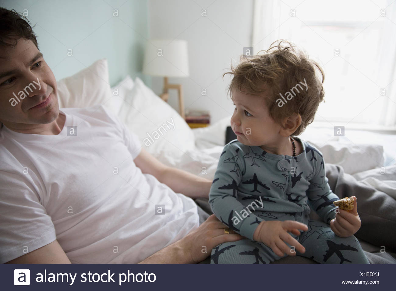 Father and son in pajamas in bed - Stock Image