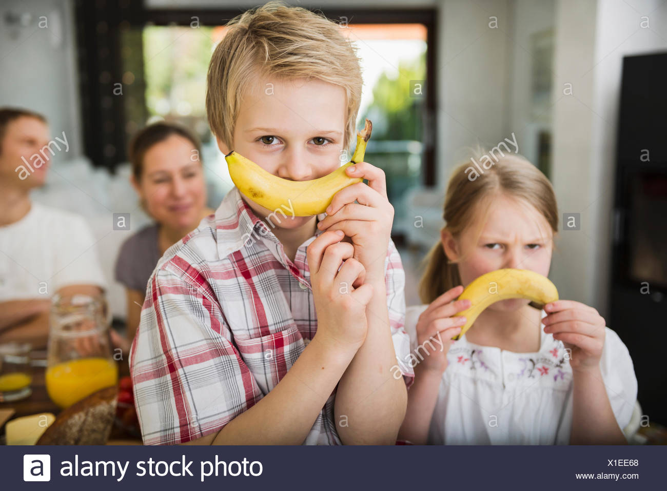 Brother and sister having fun with two bananas - Stock Image