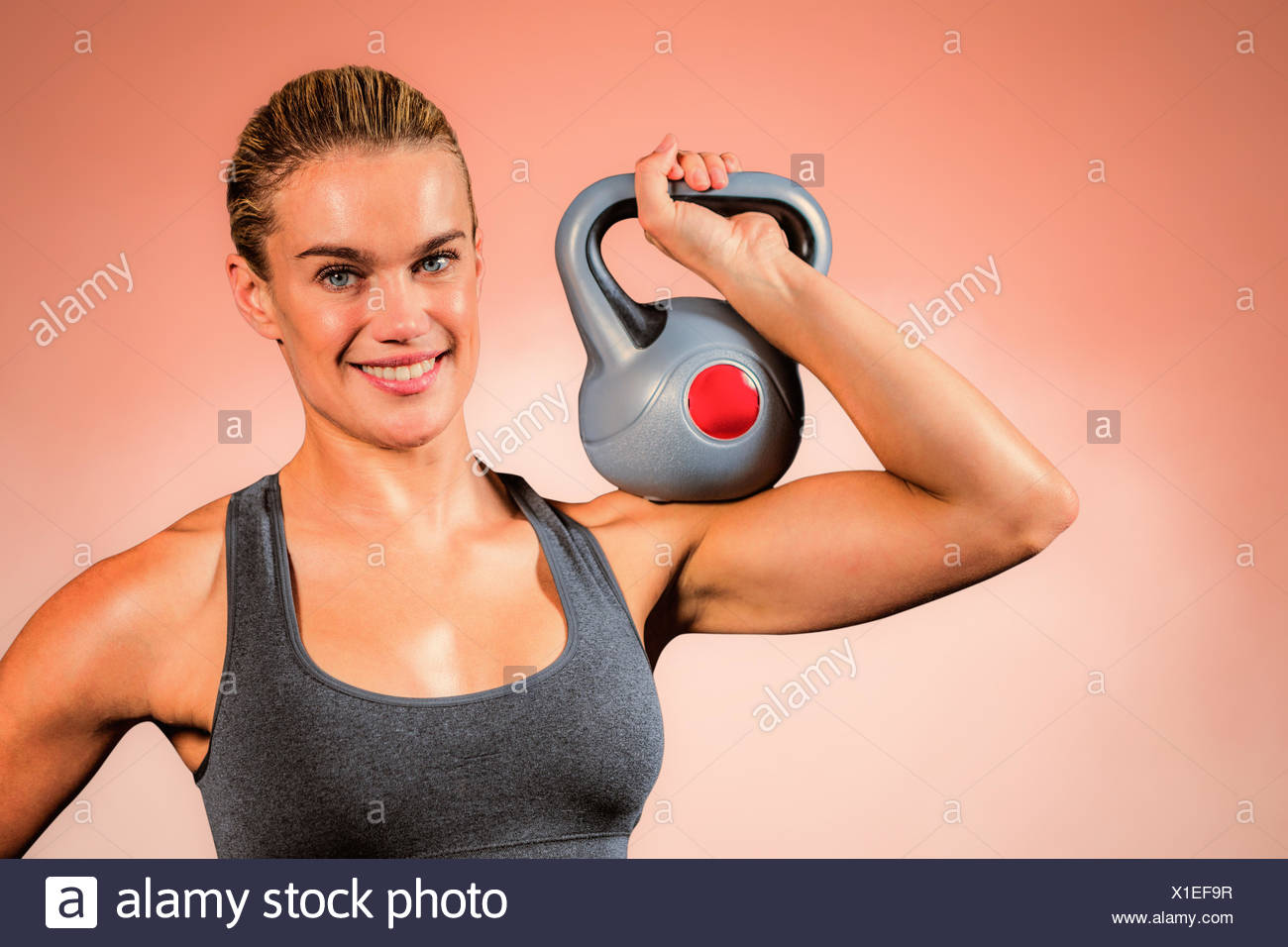 Composite image of muscular woman swinging heavy kettlebell - Stock Image