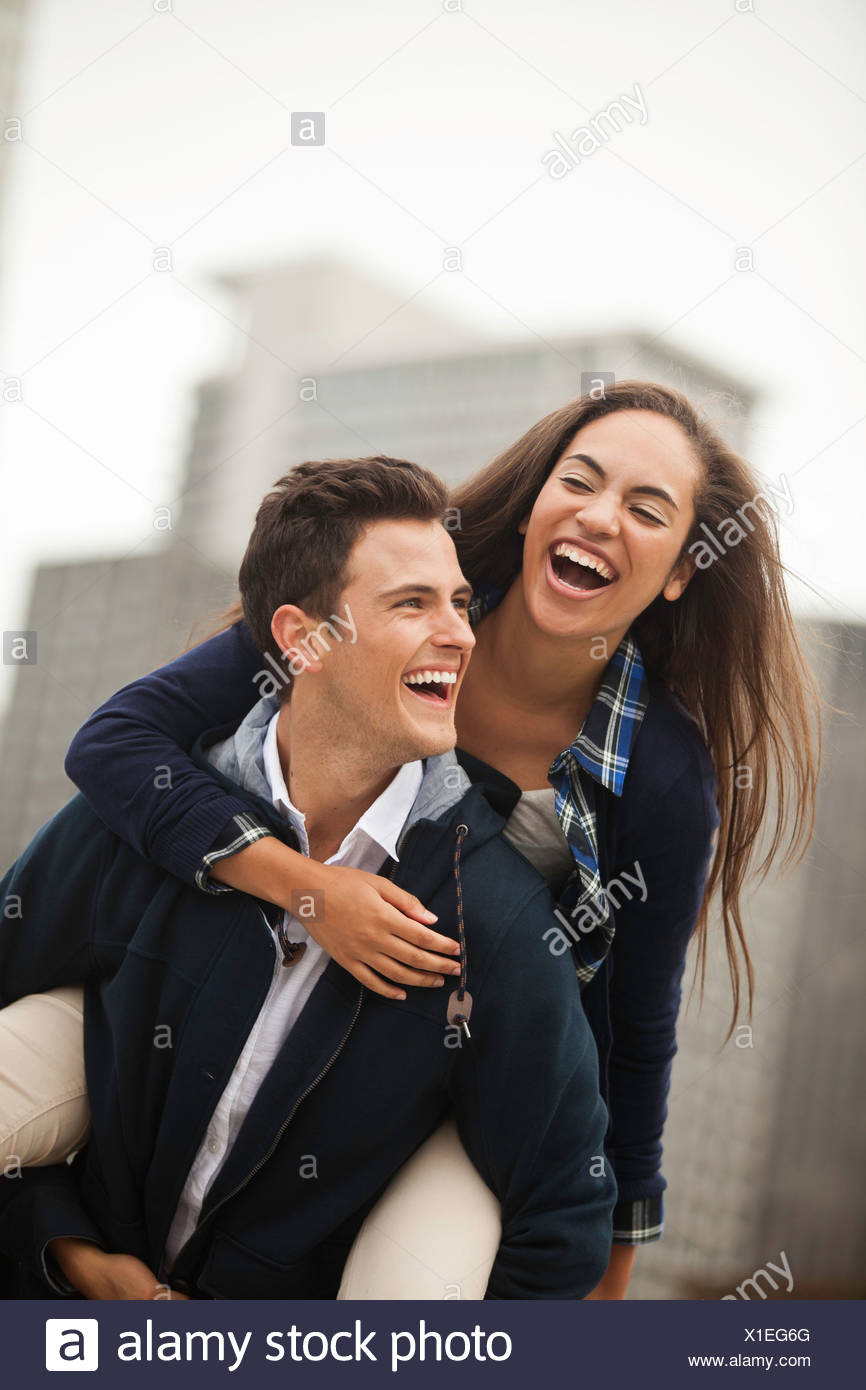Young man carrying woman on piggyback, laughing - Stock Image