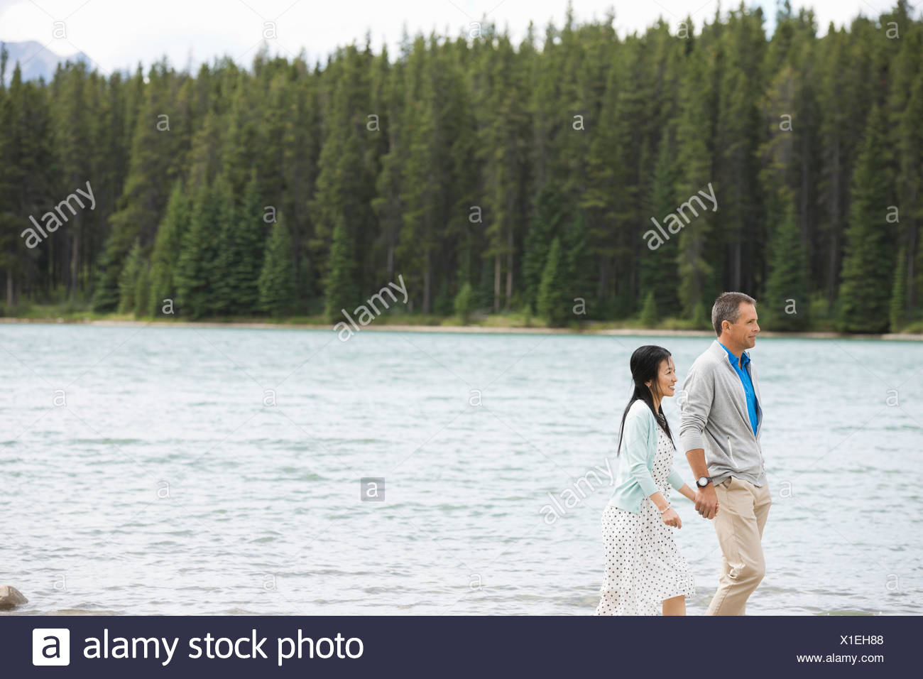Mature couple walking by the lake - Stock Image