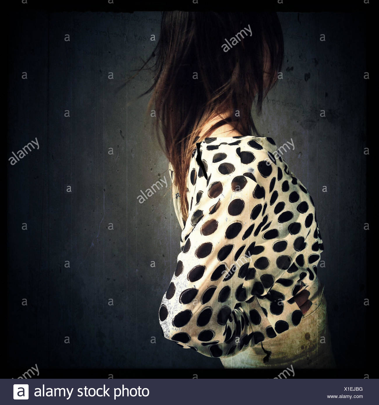Profile of woman wearing spotted shirt - Stock Image