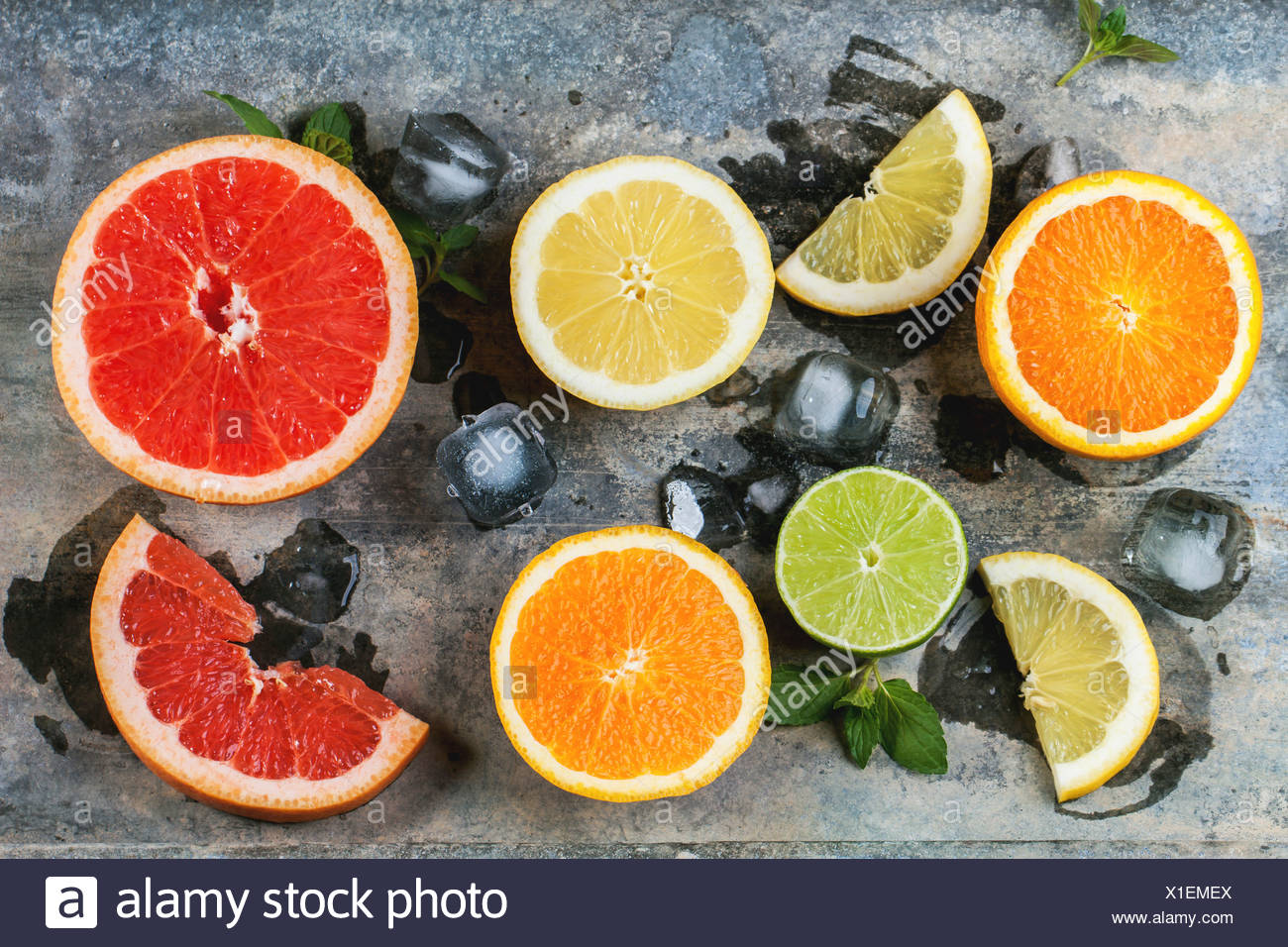 Set of sliced citrus fruits lemon, lime, orange, grapefruit with mint and ice over metal background. Top view. - Stock Image