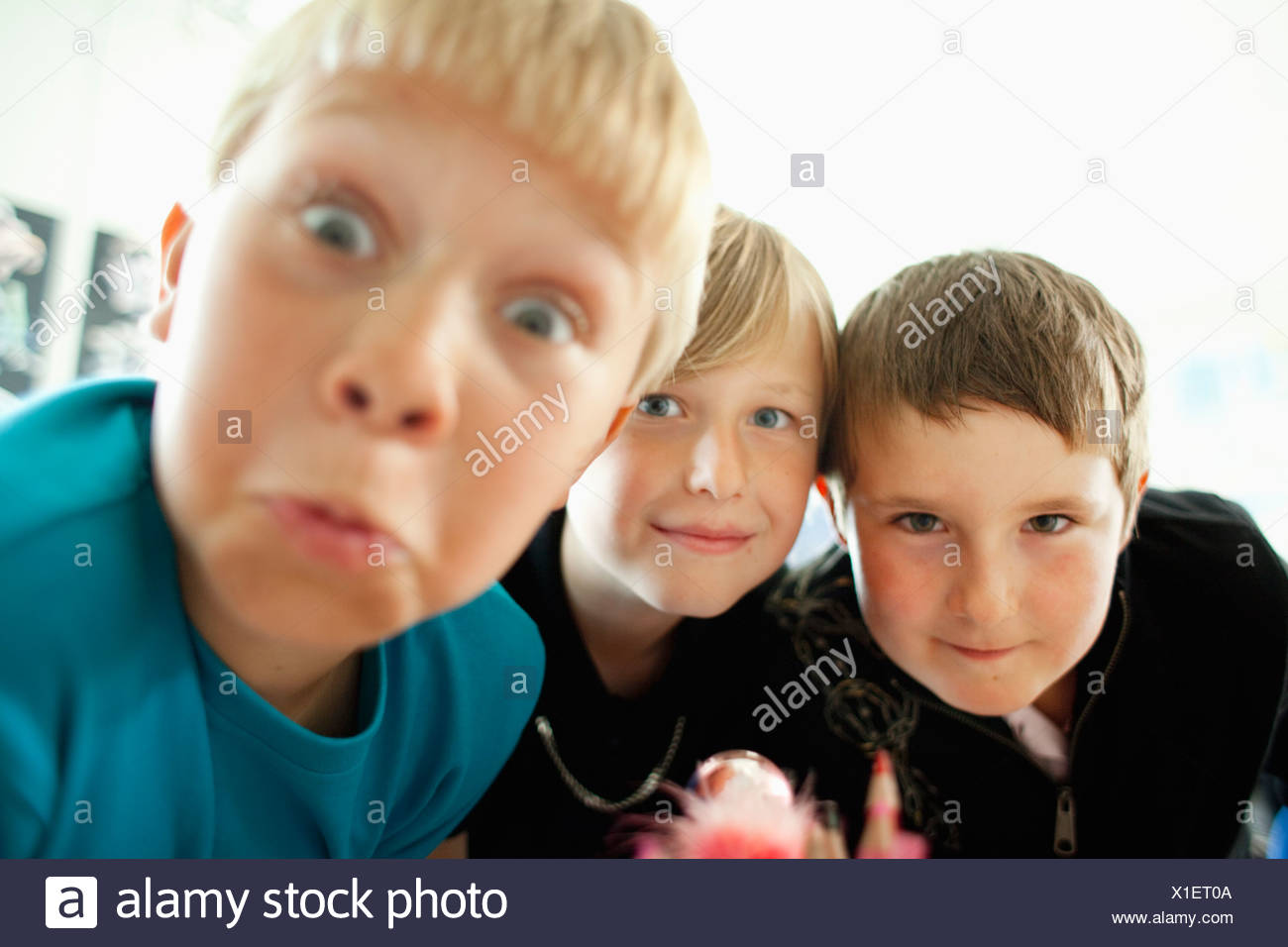 Three boys grimacing - Stock Image