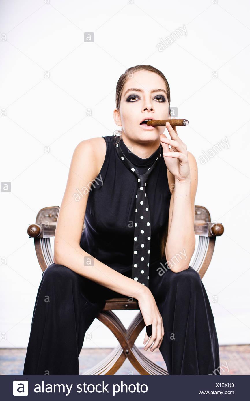 Androgynous woman smoking a cigar - Stock Image