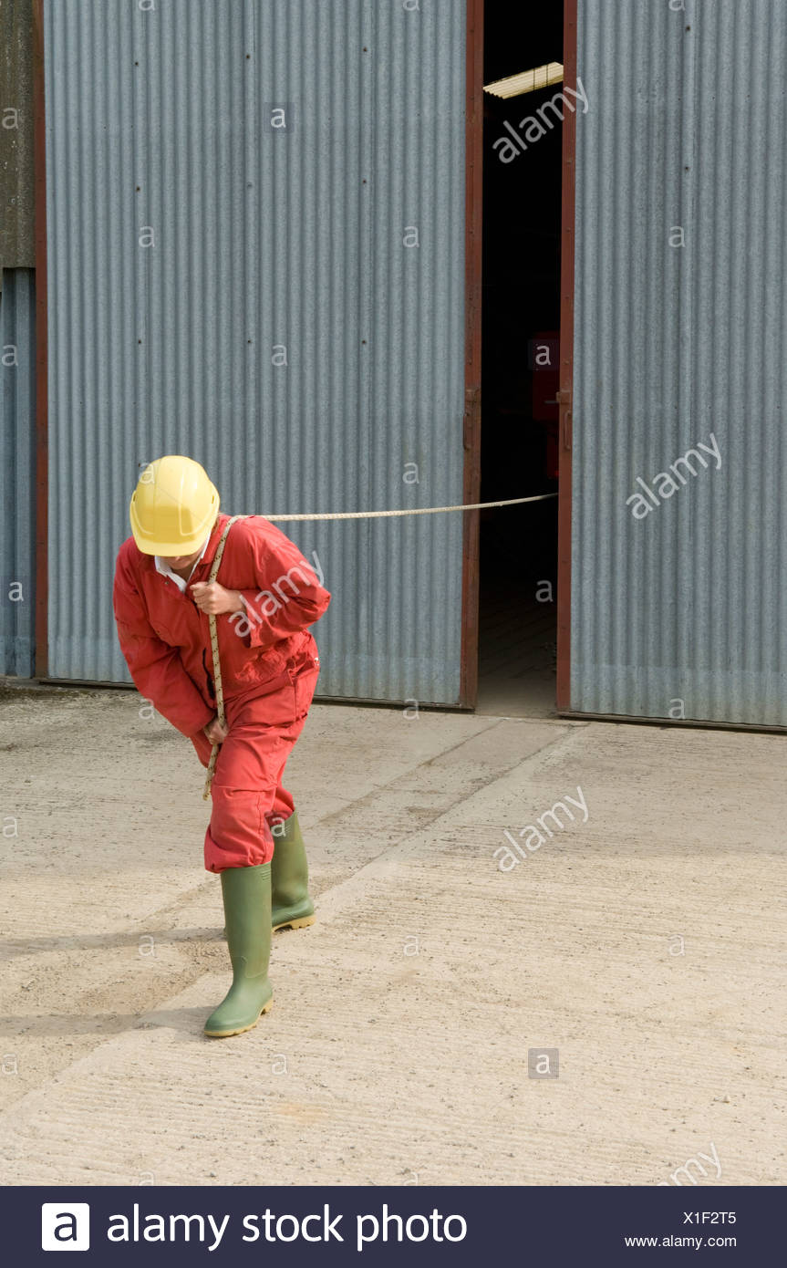 Worker pulling unseen object - Stock Image